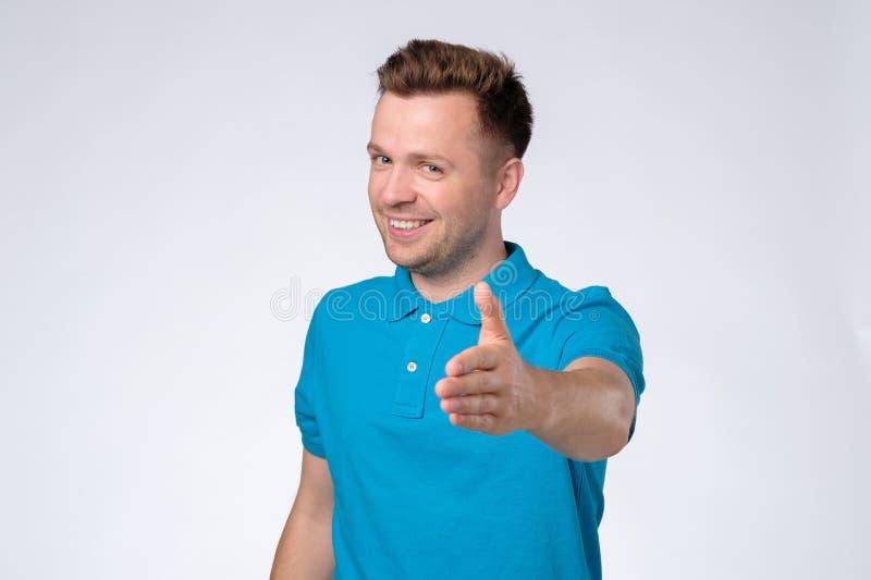 Όμορφος νεαρός άνδρας στην μπλε μπλούζα που τεντώνει έξω το χέρι για το τίναγμα στοκ φωτογραφία με δικαίωμα ελεύθερης χρήσης