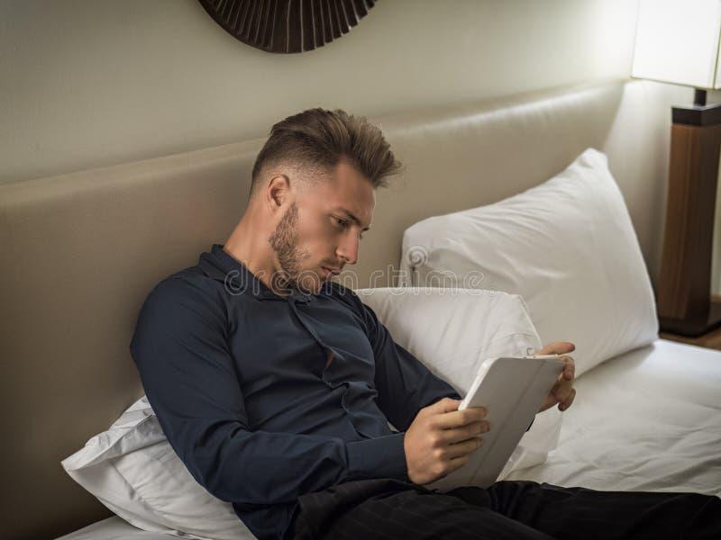 Όμορφος νεαρός άνδρας στη δακτυλογράφηση κρεβατιών στο PC ταμπλετών στοκ φωτογραφία με δικαίωμα ελεύθερης χρήσης
