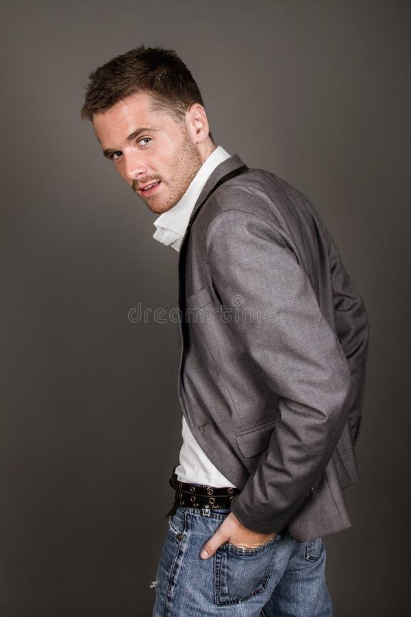 Όμορφος νεαρός άνδρας στο γκρίζο υπόβαθρο που εξετάζει τη κάμερα Portrai στοκ φωτογραφίες με δικαίωμα ελεύθερης χρήσης