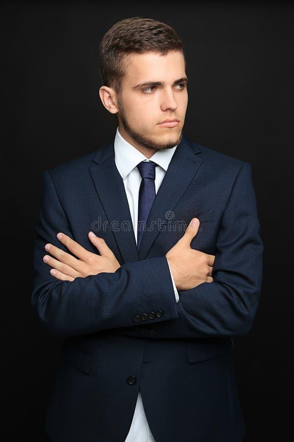 Όμορφος νεαρός άνδρας στο μοντέρνο κοστούμι στο σκοτεινό υπόβαθρο στοκ φωτογραφία