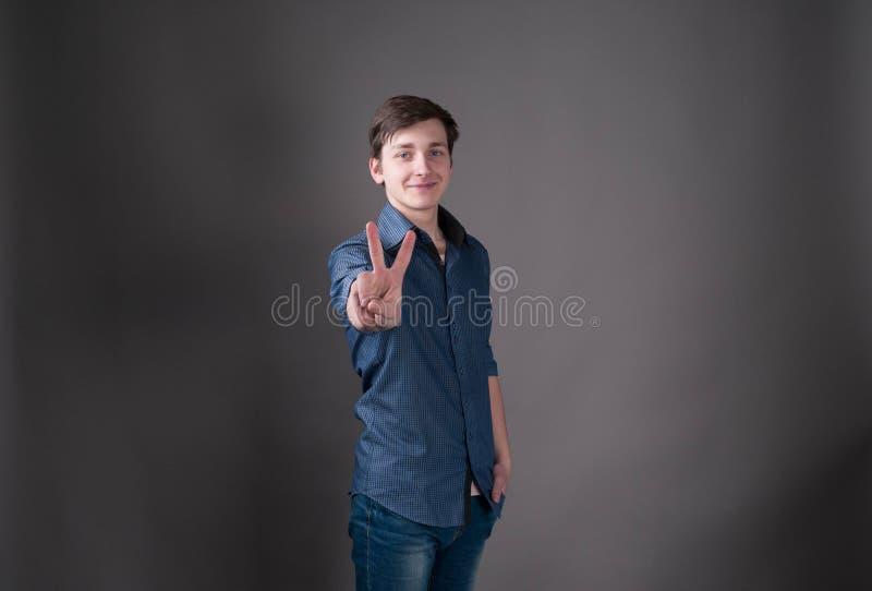 Όμορφος νεαρός άνδρας στο μπλε που εξετάζει τη κάμερα και που παρουσιάζει σημάδι ειρήνης με το χέρι στοκ εικόνα με δικαίωμα ελεύθερης χρήσης