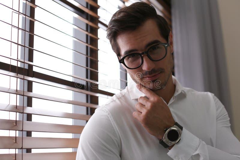 Όμορφος νεαρός άνδρας στο πουκάμισο με τα γυαλιά που στέκονται κοντά στο παράθυρο στο εσωτερικό στοκ φωτογραφίες με δικαίωμα ελεύθερης χρήσης