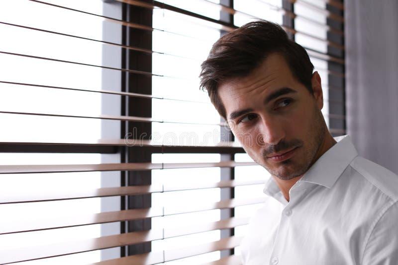 Όμορφος νεαρός άνδρας στο πουκάμισο που στέκεται κοντά στο παράθυρο στο εσωτερικό στοκ εικόνα