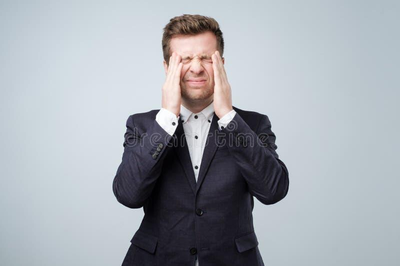 Όμορφος νεαρός άνδρας σχετικά με το κεφάλι του με το χέρι που αισθάνεται τον ισχυρό πονοκέφαλο στοκ φωτογραφίες