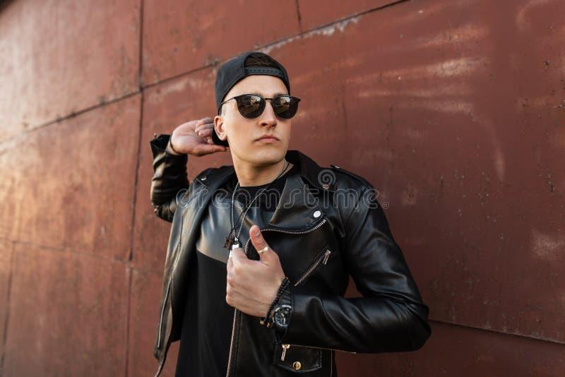 Όμορφος νεαρός άνδρας hipster σε ένα μοντέρνο μαύρο σακάκι δέρματος σε μια καθιερώνουσα τη μόδα μαύρη ΚΑΠ στα σκοτεινά μοντέρνα γ στοκ φωτογραφία με δικαίωμα ελεύθερης χρήσης