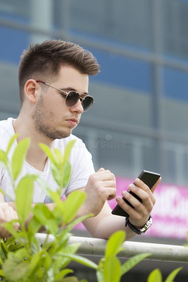 Όμορφος νεαρός άνδρας με ένα τηλεφώνημα σε ένα κινητό τηλέφωνο στοκ εικόνα