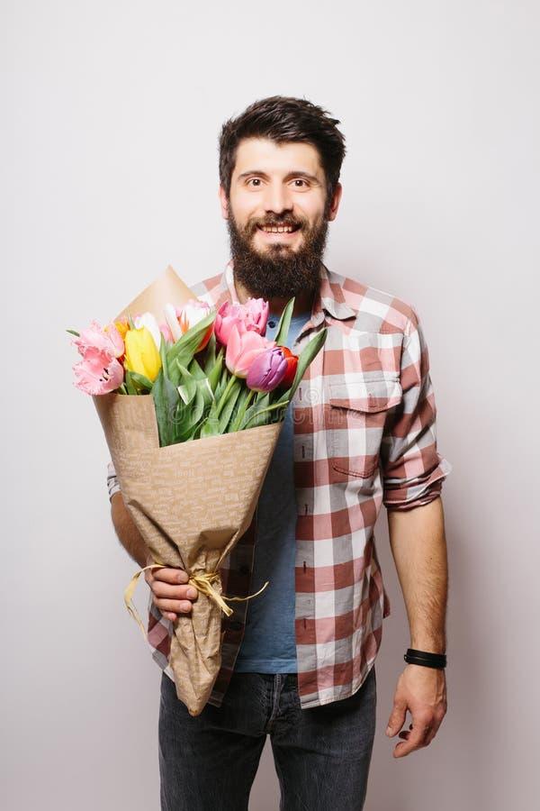 Όμορφος νεαρός άνδρας με τη γενειάδα και τη συμπαθητική ανθοδέσμη των λουλουδιών στοκ εικόνες με δικαίωμα ελεύθερης χρήσης