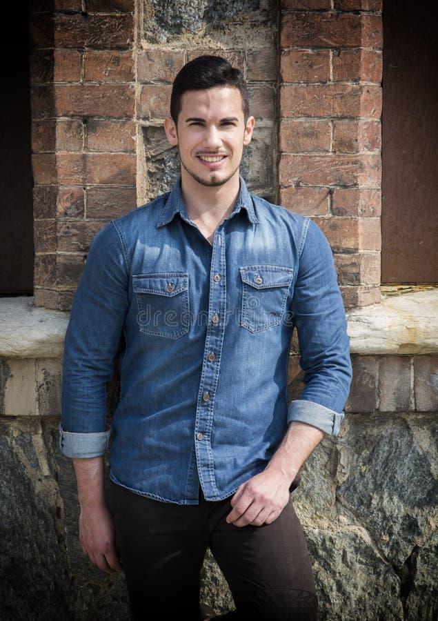 Όμορφος νεαρός άνδρας με το πουκάμισο τζιν που στέκεται υπαίθρια, χαμόγελο στοκ εικόνες με δικαίωμα ελεύθερης χρήσης