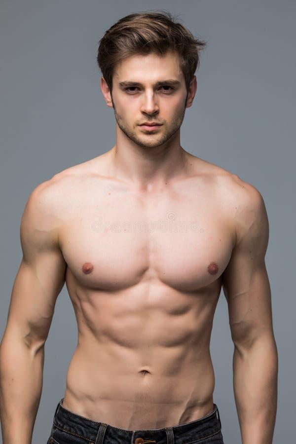 Όμορφος νεαρός άνδρας με το nude κορμό που εξετάζει τη κάμερα άνω του γκρίζου β στοκ φωτογραφίες