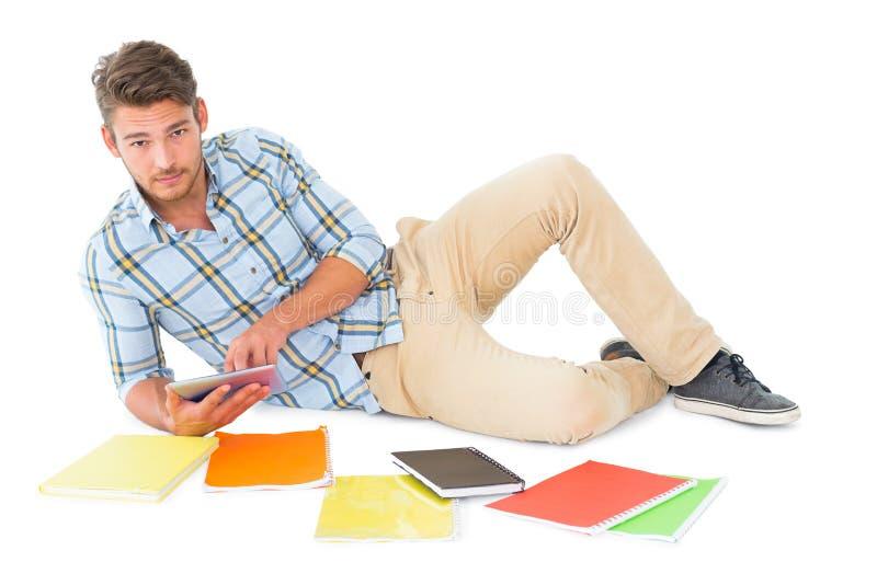 Όμορφος νεαρός άνδρας που βρίσκεται και που μελετά στοκ εικόνα με δικαίωμα ελεύθερης χρήσης