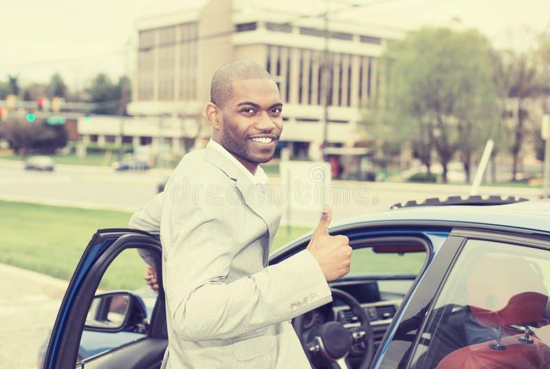 Όμορφος νεαρός άνδρας που διεγείρεται για το νέο όχημά του στοκ εικόνες