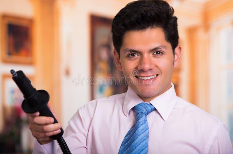 Όμορφος νεαρός άνδρας που κρατά μια ηλεκτρική σκούπα στοκ φωτογραφία με δικαίωμα ελεύθερης χρήσης