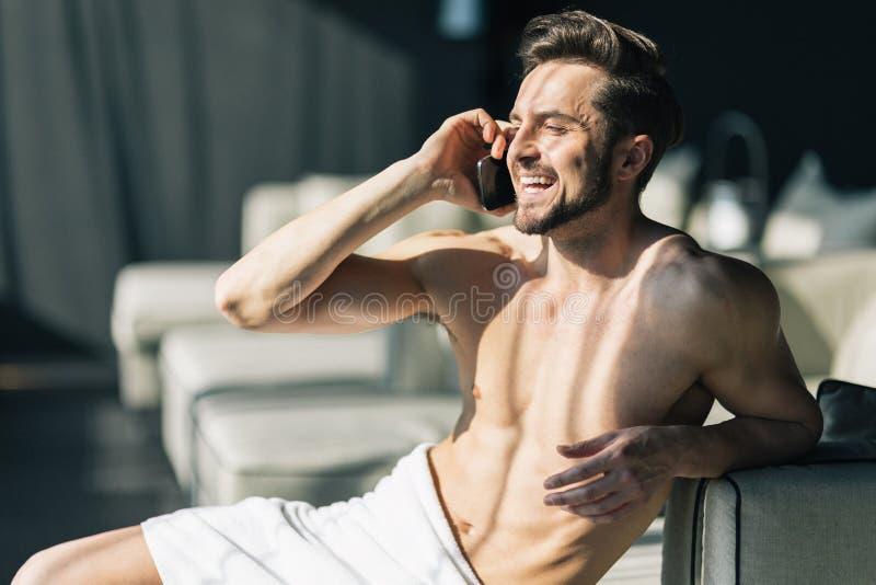 Όμορφος, νεαρός άνδρας που μιλά στο τηλέφωνο κυττάρων του το πρωί μέσα στοκ εικόνα με δικαίωμα ελεύθερης χρήσης