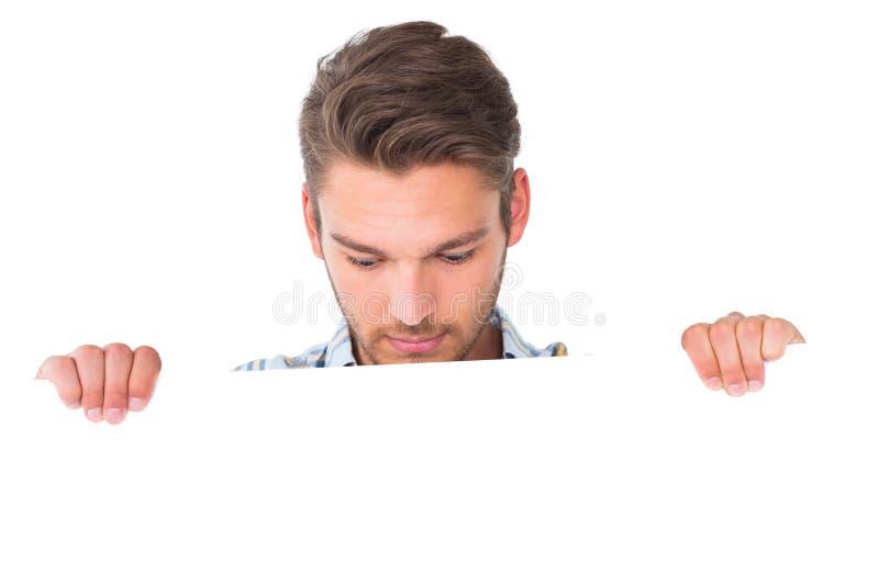 Όμορφος νεαρός άνδρας που παρουσιάζει αφίσα στοκ εικόνες