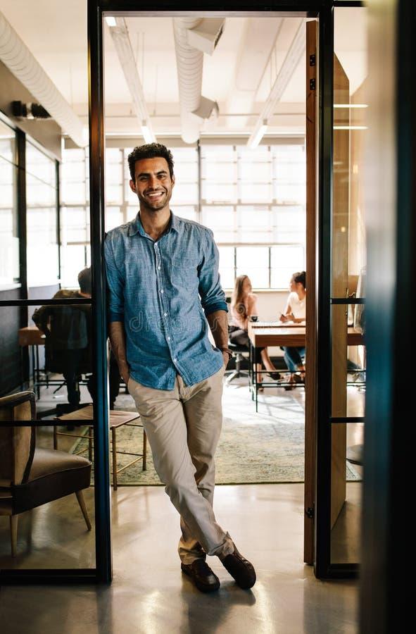 Όμορφος νεαρός άνδρας που στέκεται στην πόρτα γραφείων στοκ φωτογραφία με δικαίωμα ελεύθερης χρήσης
