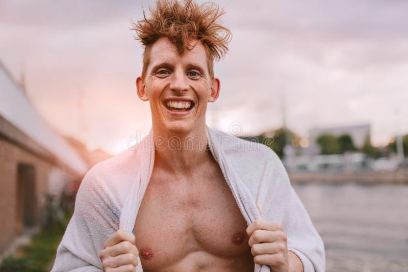 Όμορφος νεαρός άνδρας που τυλίγεται στην πετσέτα και το χαμόγελο στοκ εικόνες