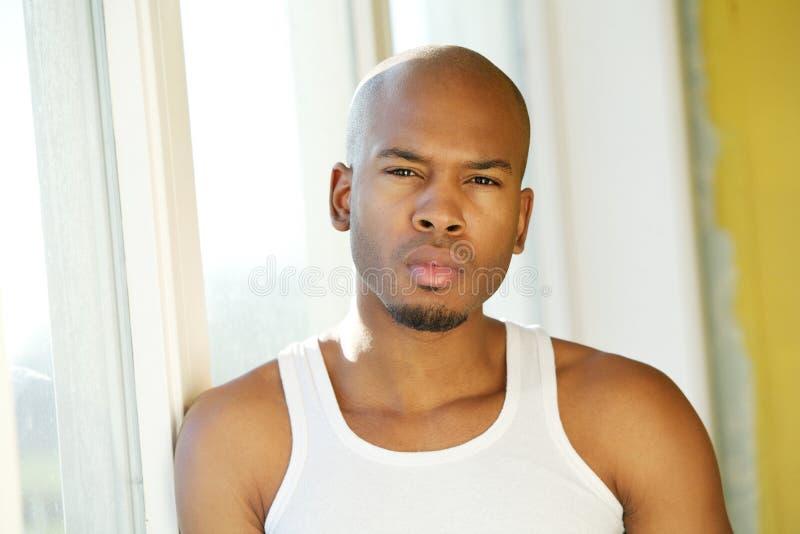 Όμορφος νεαρός άνδρας που υπερασπίζεται το παράθυρο στοκ φωτογραφίες με δικαίωμα ελεύθερης χρήσης