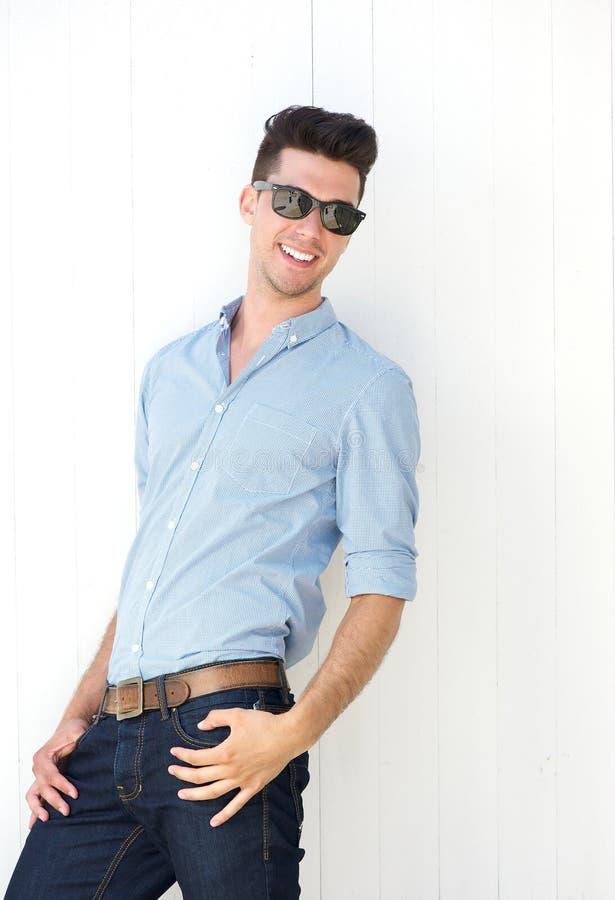 Όμορφος νεαρός άνδρας που χαμογελά με τα γυαλιά ηλίου στοκ εικόνες