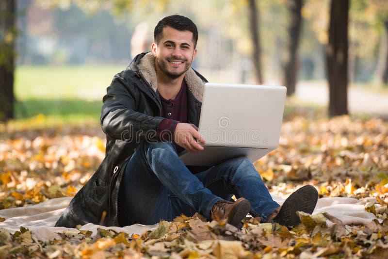 Όμορφος νεαρός άνδρας που χρησιμοποιεί το lap-top σε υπαίθριο στοκ εικόνες