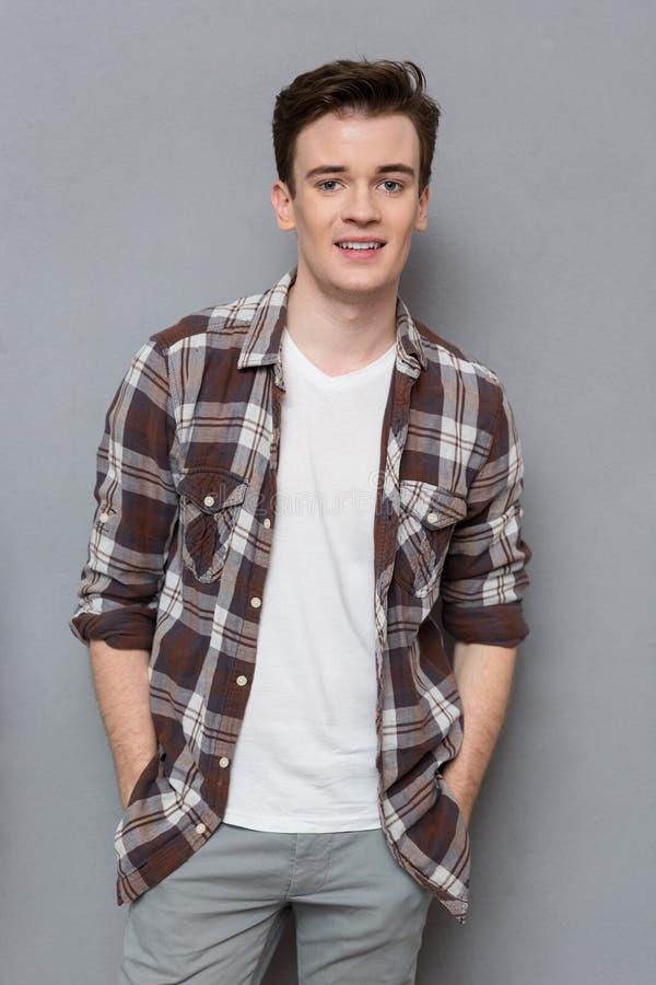 Όμορφος νεαρός άνδρας στο ελεγμένο πουκάμισο που θέτει και που χαμογελά στοκ φωτογραφίες
