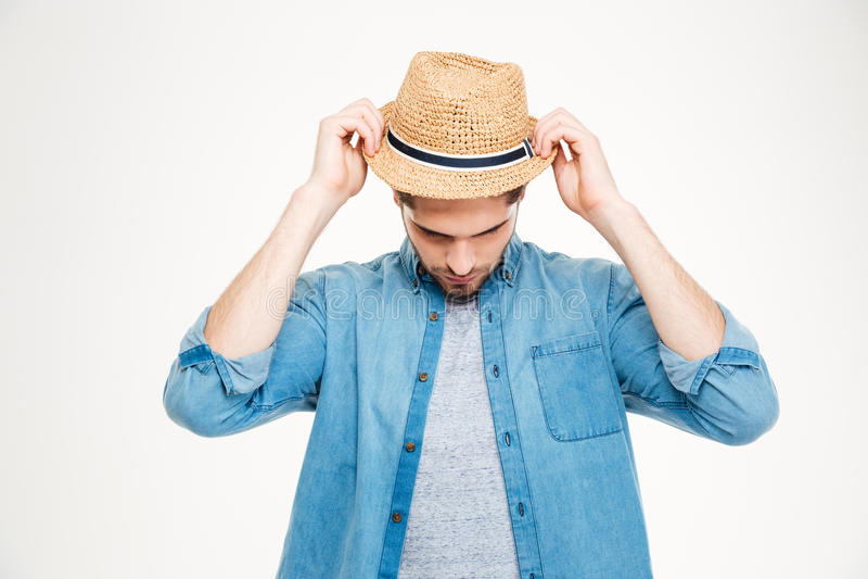 Όμορφος νεαρός άνδρας στο μπλε πουκάμισο που βάζει στο καπέλο στοκ εικόνες