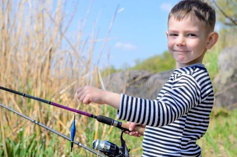 Όμορφος νεαρός που κρατά τη ράβδο αλιείας του στοκ εικόνα με δικαίωμα ελεύθερης χρήσης