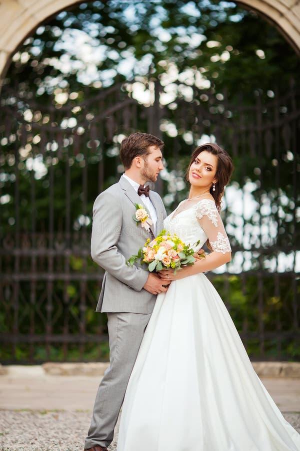 Όμορφος νεόνυμφος που αγκαλιάζει την όμορφη νύφη με την ανθοδέσμη στο ρομαντικό ευρωπαϊκό πάρκο στοκ εικόνες με δικαίωμα ελεύθερης χρήσης