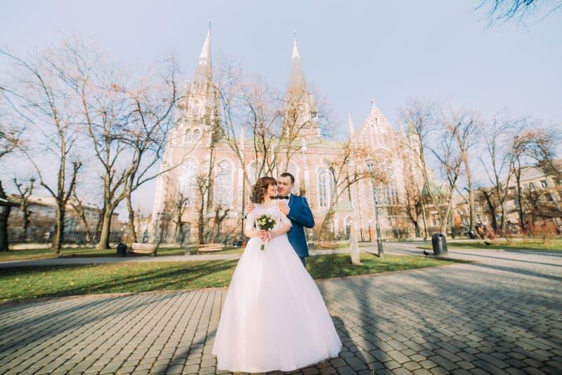 Όμορφος νεόνυμφος που αγκαλιάζει την αισθησιακή νύφη από πίσω στο υπόβαθρο μιας καταπληκτικής γοτθικής εκκλησίας στοκ εικόνα