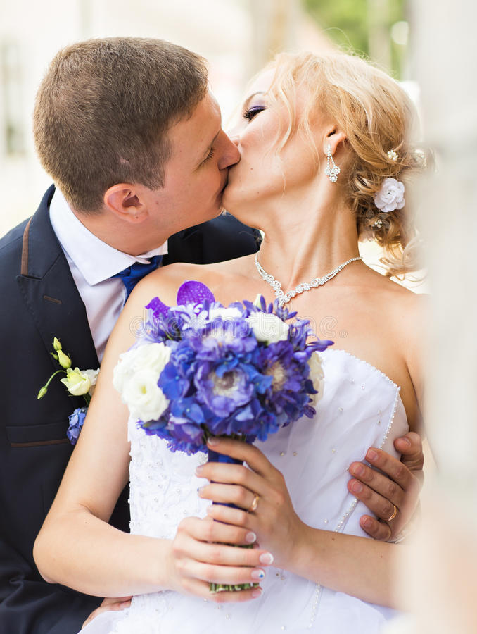 Όμορφος νεόνυμφος brunette που φιλά την όμορφη νύφη στο γαμήλιο φόρεμα στοκ εικόνες