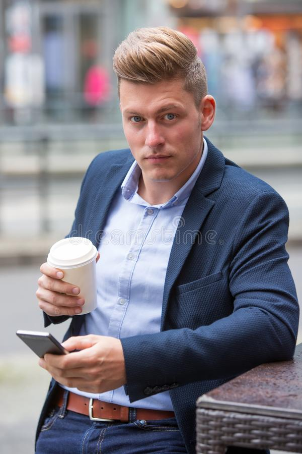 Όμορφος ξανθός επιχειρηματίας που στέκεται έξω από το κράτημα ενός τηλεφώνου στοκ εικόνα με δικαίωμα ελεύθερης χρήσης