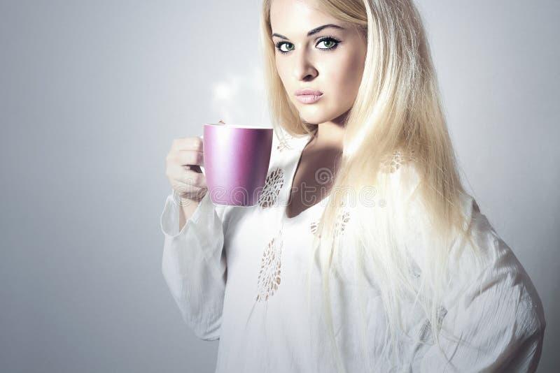Όμορφος ξανθός καφές κατανάλωσης γυναικών. Φλυτζάνι του τσαγιού στοκ φωτογραφίες
