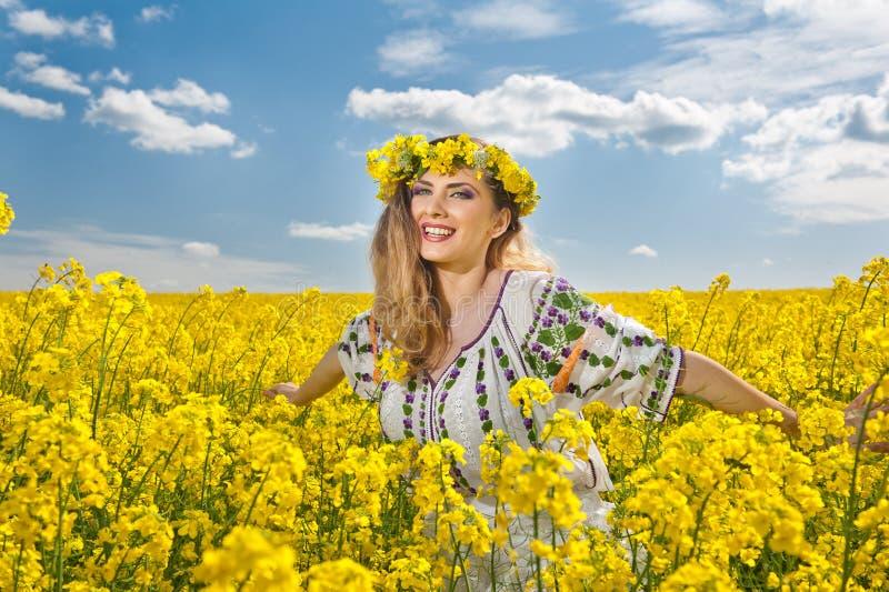 Όμορφος ξανθός με τα μπλε μάτια που χαμογελούν στον τομέα συναπόσπορων στοκ εικόνα με δικαίωμα ελεύθερης χρήσης