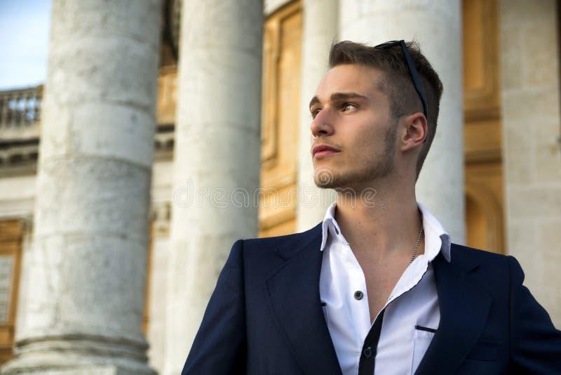 Όμορφος ξανθός νεαρός άνδρας με τις μαρμάρινες στήλες πίσω από τον στοκ εικόνα