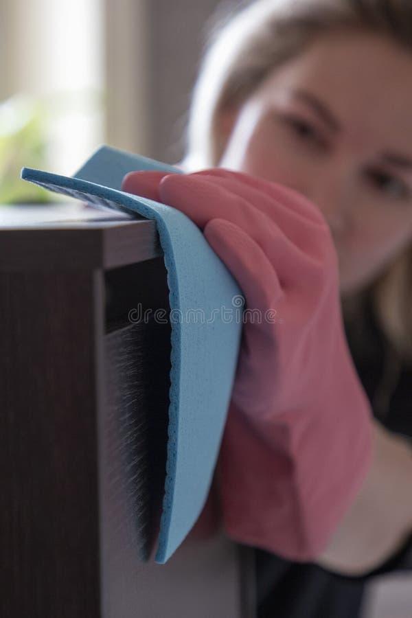 Όμορφος ξανθός στα λαστιχένια γάντια και με ένα κουρέλι σκουπίζει τη σκόνη στοκ εικόνες