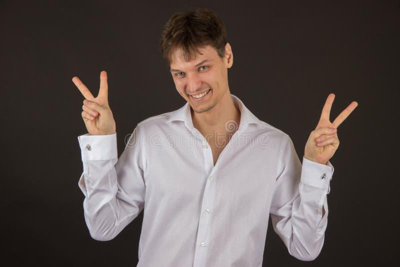 Όμορφος ομοφυλοφιλικός τύπος που χαμογελά σε ένα πουκάμισο σε ένα μαύρο υπόβαθρο στοκ εικόνα
