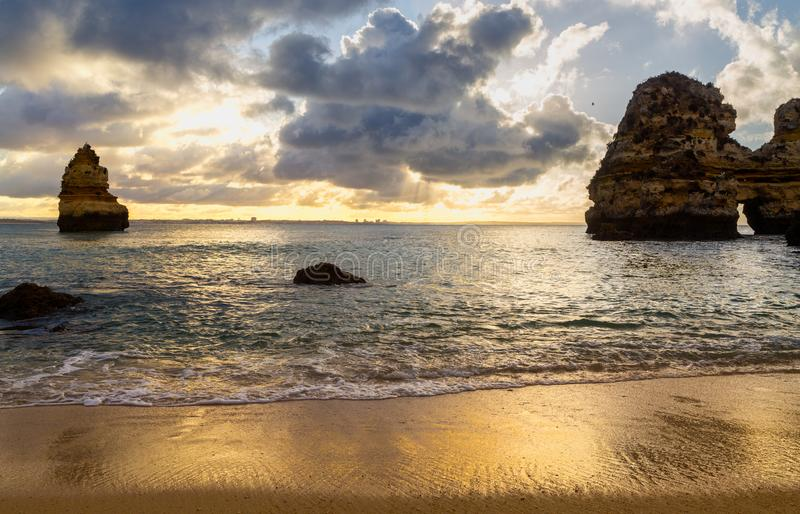 Όμορφος ορίζοντας άποψης του Ατλαντικού Ωκεανού με την αμμώδεις παραλία, τους βράχους και τα κύματα στην ανατολή στοκ εικόνα
