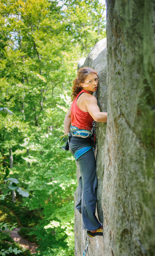 Όμορφος ορειβάτης γυναικών που αναρριχείται στον απότομο βράχο με το σχοινί στοκ εικόνα
