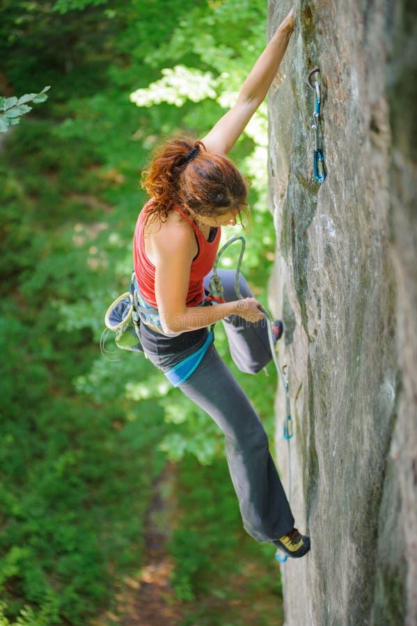 Όμορφος ορειβάτης γυναικών που αναρριχείται στον απότομο βράχο με το σχοινί στοκ φωτογραφία με δικαίωμα ελεύθερης χρήσης