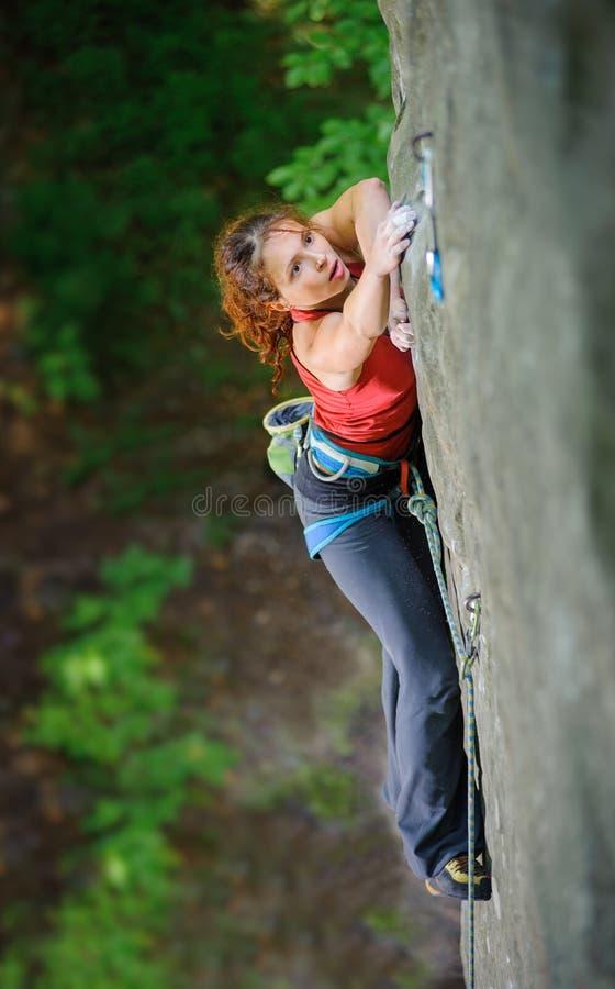 Όμορφος ορειβάτης γυναικών που αναρριχείται στον απότομο βράχο με το σχοινί στοκ φωτογραφίες