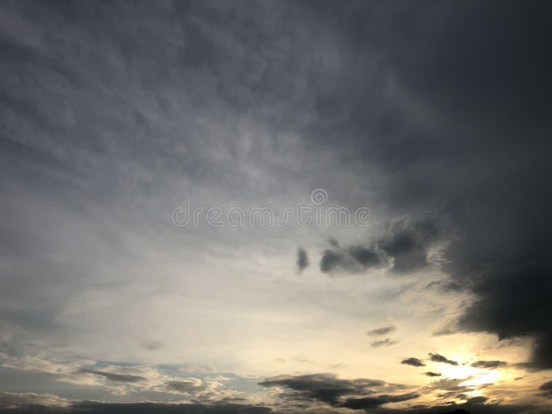 Όμορφος ουρανός που χρωματίζεται από τον ήλιο που αφήνει τις φωτεινές χρυσές σκιές Πυκνά σύννεφα στον ουρανό λυκόφατος το βράδυ Ε στοκ φωτογραφία με δικαίωμα ελεύθερης χρήσης
