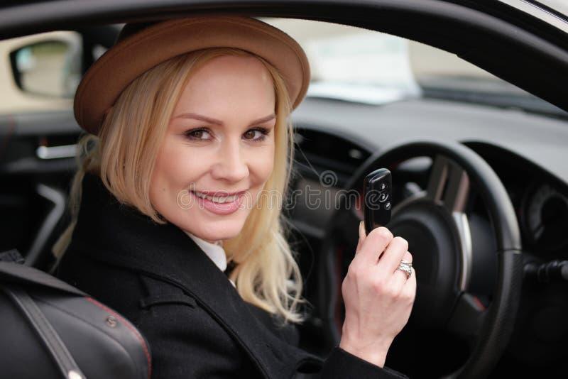 Όμορφος οδηγός γυναικών που κρατά το κλειδί αυτοκινήτων της στο αυτοκίνητο στοκ εικόνες