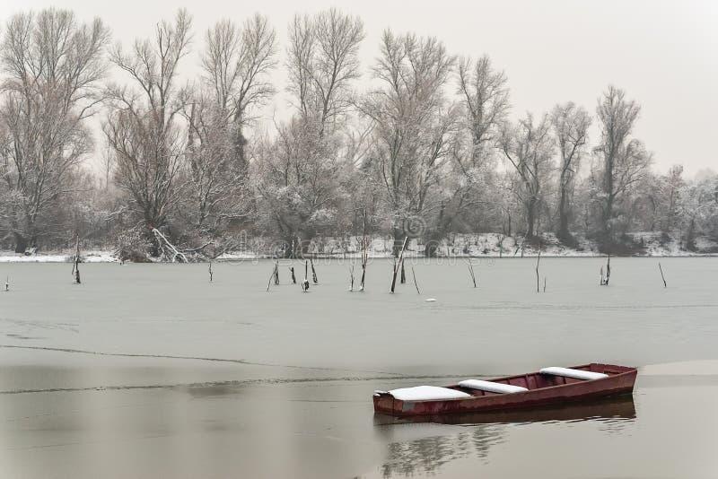 Όμορφος παγωμένος ποταμός Βάρκες που καλύπτονται με το χιόνι στοκ φωτογραφία