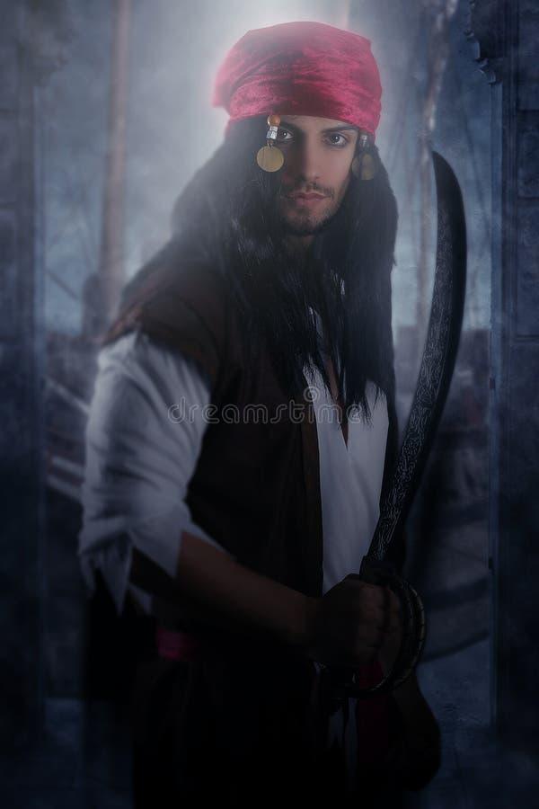 Όμορφος πειρατής που κρατά ένα ξίφος στοκ φωτογραφία