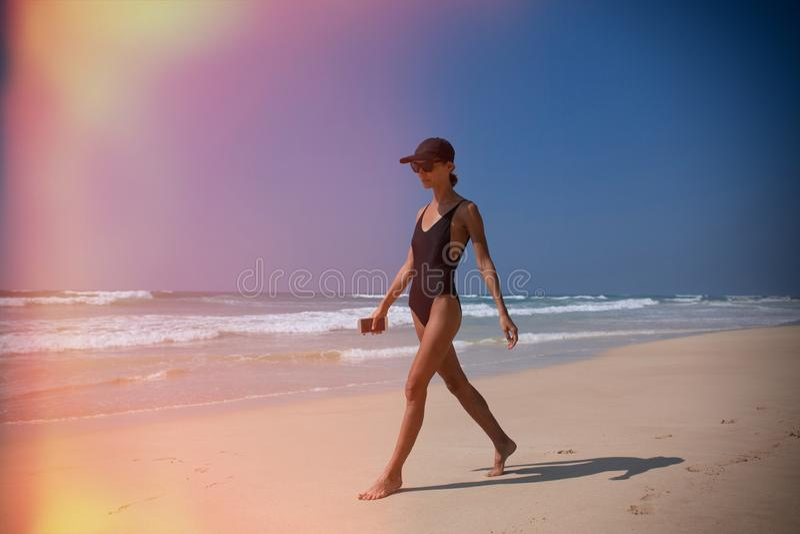 Όμορφος περίπατος κοριτσιών στην παραλία στον ωκεανό με το τηλέφωνο στοκ εικόνα