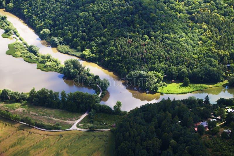 Όμορφος ποταμός που περιβάλλεται από τα δάση και τους τομείς άνωθεν στοκ εικόνες