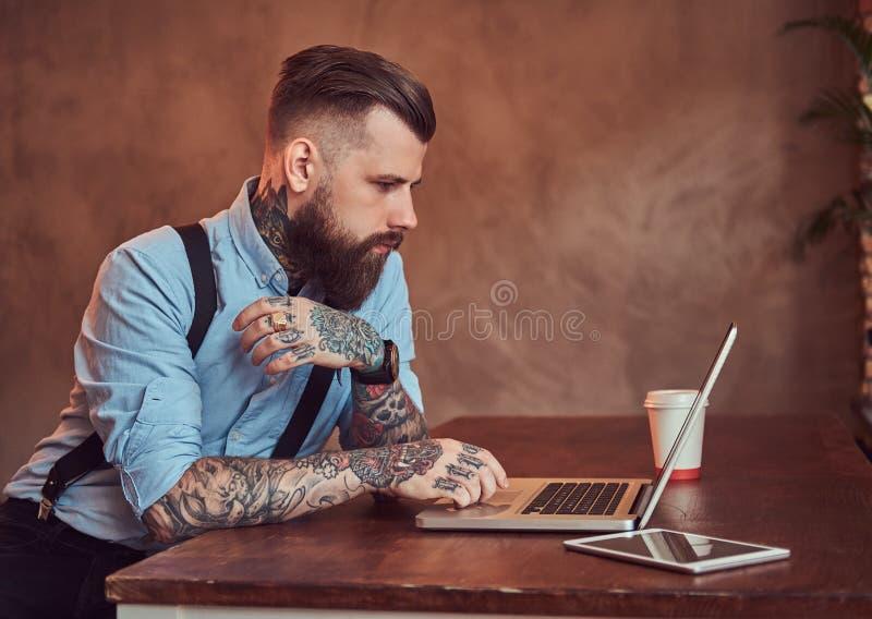 Όμορφος που διαστίζεται hipster σε ένα πουκάμισο και suspenders που κάθονται στο γραφείο, που λειτουργεί σε ένα lap-top, σε ένα γ στοκ φωτογραφία με δικαίωμα ελεύθερης χρήσης