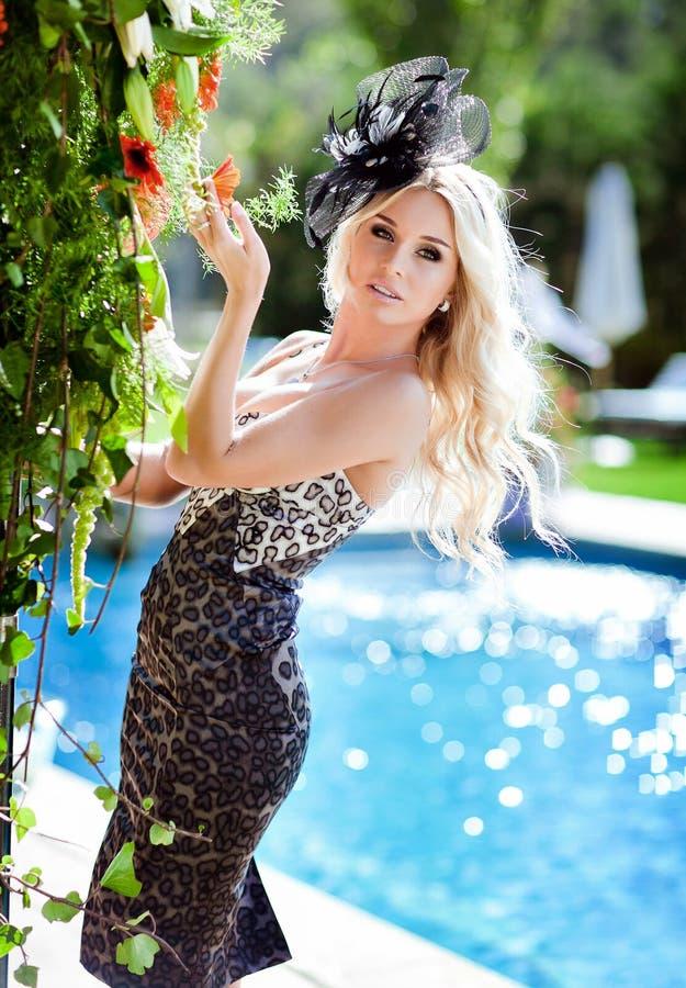Όμορφος προκλητικός ξανθός με τη μεγάλη αποτυχία στο φόρεμα τυπωμένων υλών λεοπαρδάλεων και το α στοκ φωτογραφία