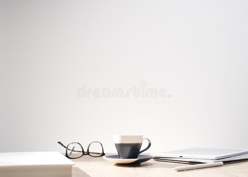 Όμορφος πυροβολισμός των οπτικών γυαλιών και ένα φλυτζάνι σε έναν πίνακα με ένα άσπρα υπόβαθρο και ένα διάστημα για το κείμενο στοκ εικόνα