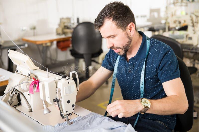 Όμορφος ράφτης που χρησιμοποιεί μια ράβοντας μηχανή στοκ εικόνες