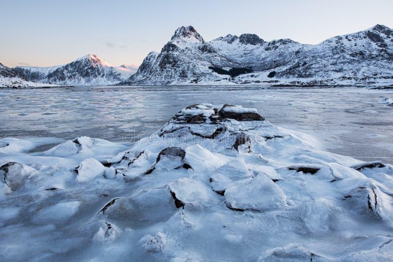 Όμορφος ραγίζοντας πάγος τοπίων, παγωμένη παραλία με το υπόβαθρο κορυφογραμμών βουνών στην ανατολή στη χειμερινή εποχή, νησιά Lof στοκ φωτογραφία με δικαίωμα ελεύθερης χρήσης